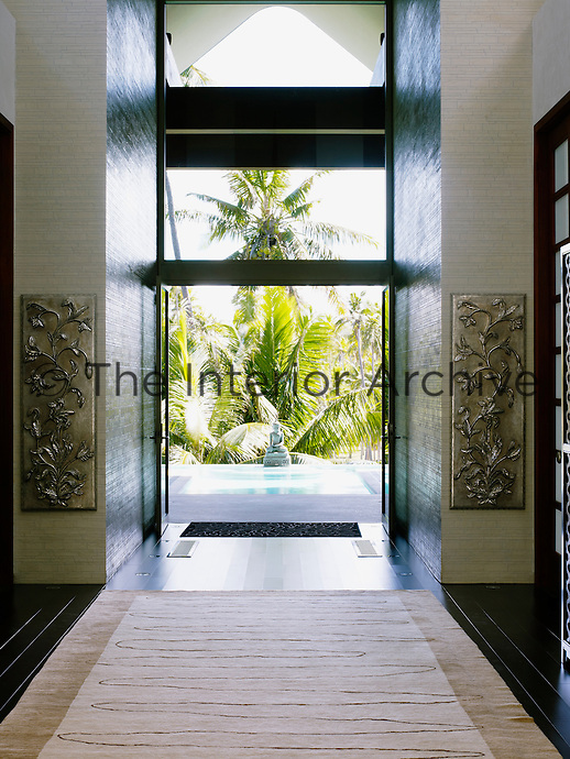 Double glass doors herald the entrance to the beach house which has stained black wooden floors and walls sheathed in local stone
