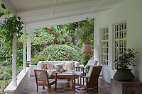 The veranda is laid with handmade floor tiles and furnished with 1940s rattan armchairs