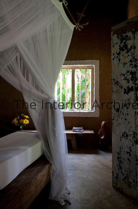 The bedrooms are simply furnished with a rustic bed draped in mosquito netting