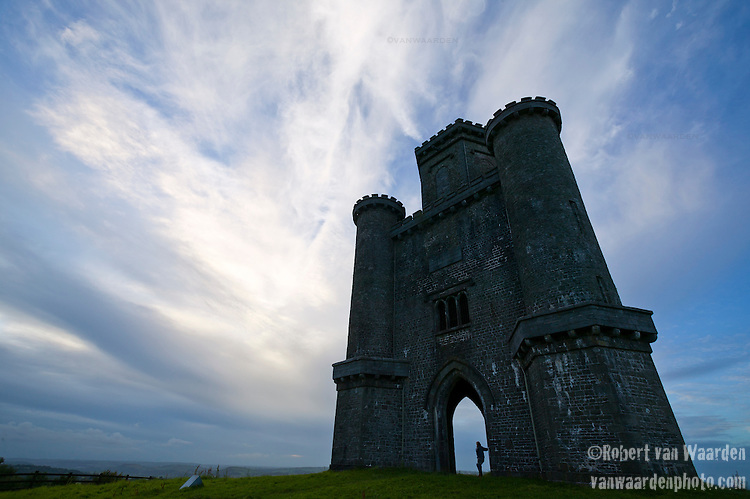A female figure stands beneath Paxton's Tower in Wales, the United Kingdom. Paxton's Tower is a castle like building belonging to the Landmark Trust, a United Kingdom building preservation charity that rescues historic buildings at risk and gives them a new life as places to stay in and experience.