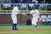 Nathan Esposito (7) of the Burlington Royals shakes hands with third base coach Scott Thorman (16) after hitting a home run against the Princeton Rays at Burlington Athletic Stadium on August 12, 2016 in Burlington, North Carolina.  The Royals defeated the Rays 9-5.  (Brian Westerholt/Four Seam Images)