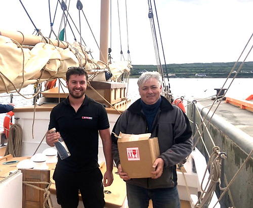 in the Aran islands, Aonghus Mullen of Kilronan takes delivery of a cargo of goodies from Gary Mac Mahon aboard Ilen after the historic passage from Foynes