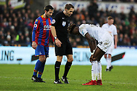 Referee Craig Pawson (C) sees to Tammy Abraham of Swansea City (R) who suffered an injury during the Premier League match between Swansea City and Crystal Palace at The Liberty Stadium, Swansea, Wales, UK. Saturday 23 December 2017