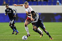 John Wolyniec (15) of the New York Red Bulls attempts to hold off Kenny Mansally (7) of the New England Revolution. The New York Red Bulls defeated the New England Revolution 3-0 during a U. S. Open Cup qualifier round match at Red Bull Arena in Harrison, NJ, on May 12, 2010.