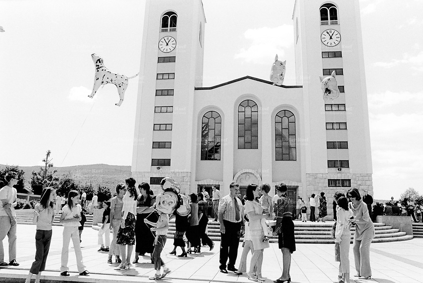 Bosnia. Medjugorje. Pilgrimage. Center of prayers. Shrine of the Queen of Peace, the Virgin Mary. The church was consecrated on january 19 1969. Today it is the focal point of prayer life and place of gathering for the parishioners and pilgrims. The holy mass and the prayer programme take place in the church.  On a sunny sunday morning, after a mass in croatian language, a group of children hold in their hands blown up ballons in the shape of a dog, a mouse named Mickey and Pikachu, etc. © 2002 Didier Ruef