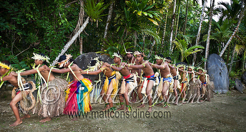Talented traditional dancers form a  konga line in front of stone money in Yap Micronesia (Photo by Matt Considine - Images of Asia Collection) (Matt Considine)