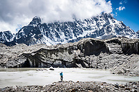 A hiker on the rock glacier near Gokyo, stands above a glacial lake while hiking to Cho La Pass, Nepal.