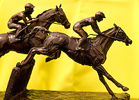 A bronzed piece of art showing two jockey's jumping a hurdle during the Queen's Cup Steeplechase in Mineral Springs, NC.