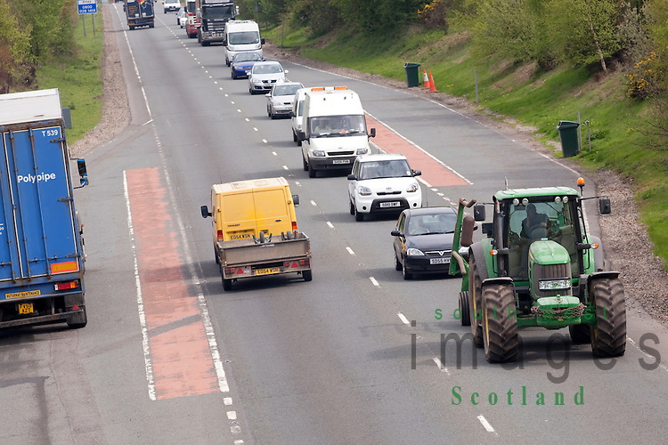A queue of traffic behind a tractor on the A75 road near Dumfries Dumfries and Galloway Scotland UK