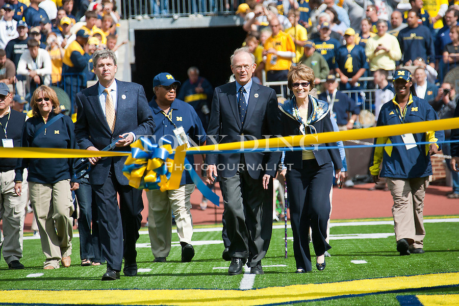 Front left to right, Michigan Athletic Director David Brandon, former Athletic Director Bill Martin, and University President Mary Sue Coleman, walk towards a ribbon-cutting ceremony to re-dedicate Michigan stadium, before an NCAA college football game, Saturday, Sept. 4, 2010, in Ann Arbor, Mich. After a three year, $226 Million renovation, the Big House is now bigger than ever, reclaiming the country's title as largest college football stadium in capacity. (AP Photo/Tony Ding)