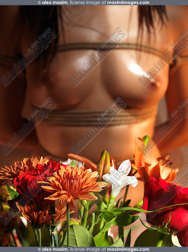 Flowers in front of a Beautiful nude asian woman body tied with Japanese Shibari rope bondage