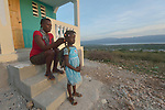 Noelsaint Dieutela braids the hair of her daughter Cherlyna Joseph, 6, as she prepares to walk to school in the morning. They live in a new house built by Servicio Social de las Iglesis Dominicanas in the Haitian community of Ganthier. SSID, a member of the ACT Alliance, has worked extensively in the community since it was devastated in 2016 by Hurricane Matthew.