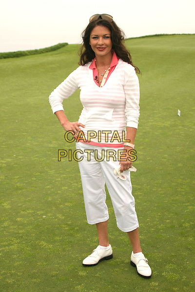 CATHERINE ZETA-JONES.9th Annual Michael Douglas & Friends Celebrity Golf Event at the Trump National Golf Club, Rancho Palos Verdes, California, USA..sport full length white pink striped stripes top cropped beige trousers hand on hip.CAP/ADM/BP.©Byron Purvis/AdMedia/Capital Pictures