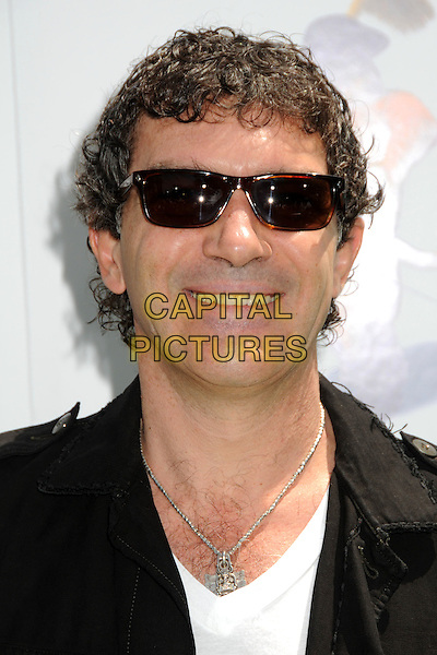 "ANTONIO BANDERAS .Attending the ""Shrek Forever After"" Los Angeles Film Premiere held at the Gibson Amphitheatre, Universal City, California, USA, 16th May 2010..arrivals portrait headshot black white silver necklace curly hair ray bans sunglasses wayfarers smiling .CAP/ADM/BP.©Byron Purvis/AdMedia/Capital Pictures."