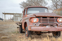 An old rusted Dodge truck parked in front of an abandoned Gas Station and Cafe in Adrian Texas on Route 66.