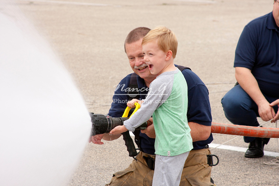A young boy using a fire hose to spray water with a firefighter