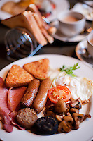 A full Irish breakfast with sausages, bacon, black and white puddings, mushroom, tomato, hash browns, and a rack of toast and, of course, strong tea.