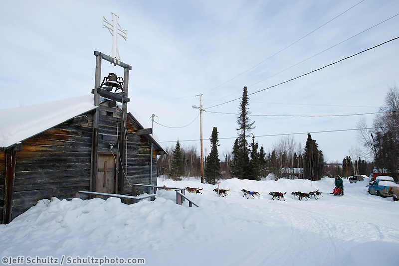 Jake Berkowitz passes by St. Luke's church as he runs down the road arrivng at the Shageluk checkpoint on Saturday morning    Iditarod 2009