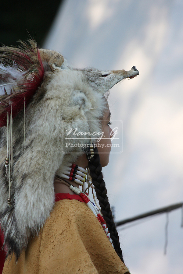 A young Native American Indian boy wearing traditional leather dress and coyote skin fur hat
