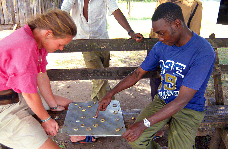 Life is a game of checkers. A German woman plays checkers made from bottlecaps with a native Kenya man while waiting for the heat to settle down in Masai Mara Reserve, Kenya, Africa.
