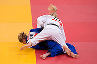 30.07.2012. London, England. Automne Pavie (FRA) in white defeats Britains Sarah Clark (GBR) in blue in the Womens 57kg Elimination Round of 32 during the Judo Preliminaries on Day 3 of the London 2012 Olympic Games at ExCeL.