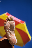 Rio de Janeiro, Brazil. A sandy foot against a parasol on the beach on a sunny day.
