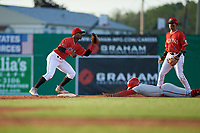 Batavia Muckdogs shortstop Samuel Castro (15) waits for a throw to force out Rafael Bautista sliding into second base as Gerardo Nunez (2) looks on during a NY-Penn League game against the Auburn Doubledays on June 18, 2019 at Dwyer Stadium in Batavia, New York.  Batavia defeated Auburn 7-5.  (Mike Janes/Four Seam Images)