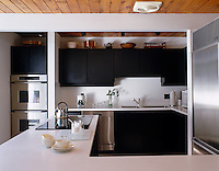 In this kitchen designed for a keen chef an L-shaped island has been installed to give ample work surface