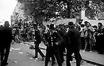 Notting Hill, London. 1976<br /> A small group of police with truncheons drawn come under attack, as a hail of bricks and bottles are thrown at them.