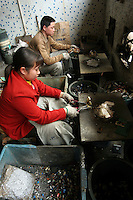 """Chinese workers """"bake"""" motherboards from e-waste in a workshop in Guiyu."""