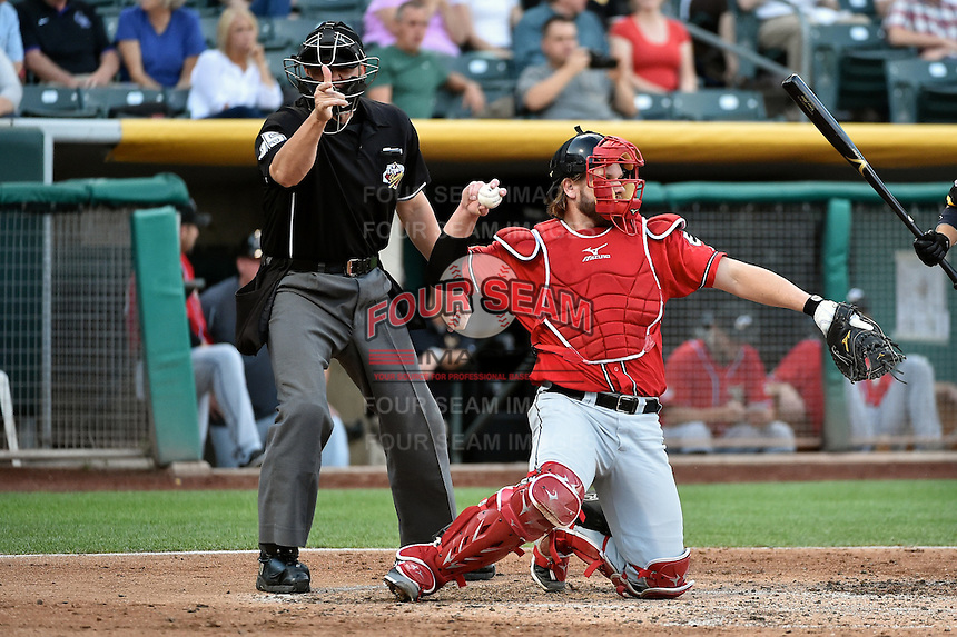 Adam Moore (12) of the El Paso Chihuahuas behind the plate with home plate umpire Brandon Henson during the game between the Chihuahuas and the Salt Lake Bees at Smith's Ballpark on August 7, 2014 in Salt Lake City, Utah.  (Stephen Smith/Four Seam Images)