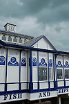Fish and Chip shop sign on Eastbourne Pier with dark threatening sky above