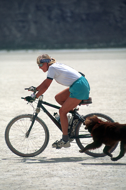 Woman mountain biking with her dog on the playa in the Black Rock Desert