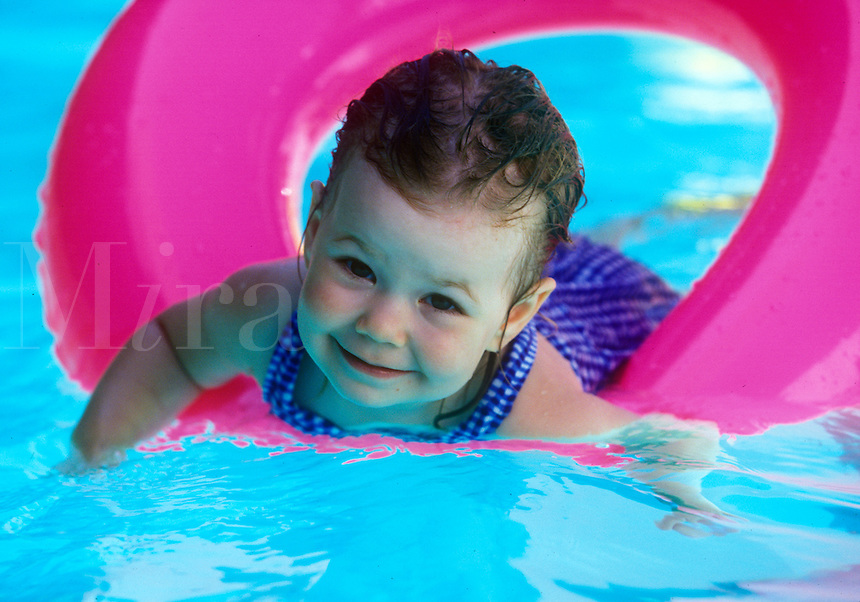Toddler swimming with pool float.
