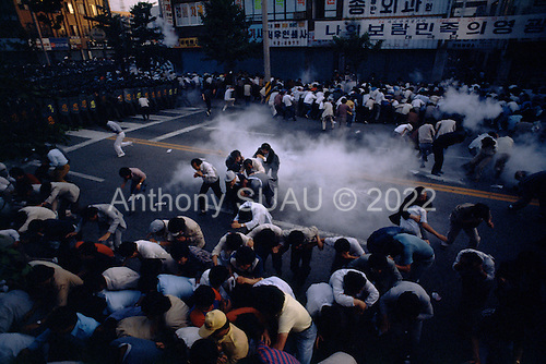 "Chunju, South Korea.May 1986..A peaceful opposition rally is dispersed by riot police with CS tear gas...After two decades of building an economic miracle, in the summer of 1987 tens of thousands of frustrated South Korean students took to the streets demanding democratic reform. ""People Power"" Korean-style saw Koreans from all social spectrums join in the protests...With the Olympics to be held in South Korea in 1988, President Chun Doo Hwan decided on no political reforms and to choose the ruling party chairman, Roh Tae Woo, as his heir. The protests multiplied and after 3 weeks Chun conceded releasing oppositionist Kim Dae Jung from his 55th house arrest and shaking hands with opposition leader Kim Young Sam. Days later he endorsed presidential elections and an amnesty for nearly 3,000 political prisoners. It marked the first genuine initiative of democratic reform in South Korea and the people had their victory."