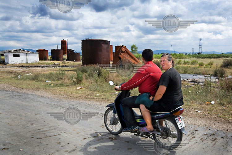 A couple drive their motorcycle through the oilfields of Fieri.