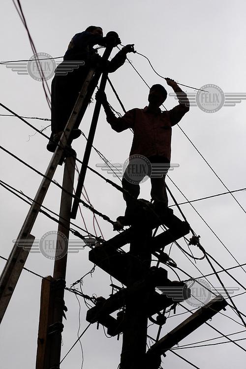 Workers attempting to repair a broken power line. Srinagar, Kashmir,India. © Fredrik Naumann/Felix Features