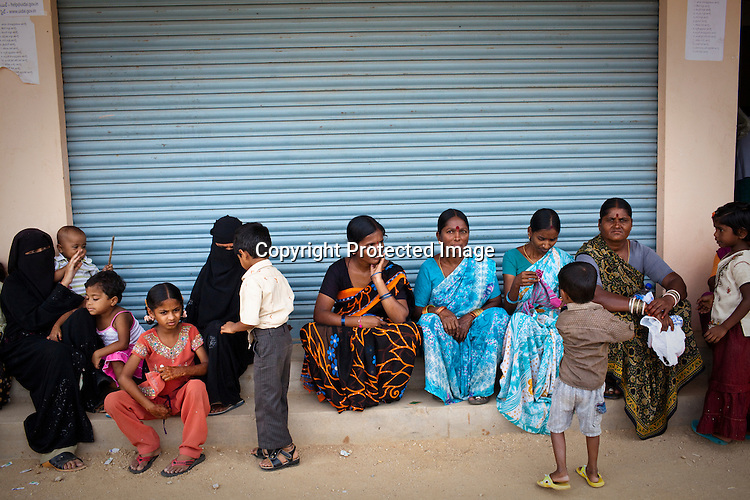 Villagers wait outside the enrollment centre in Naagaaram village, outskirts of Hyderabad in Andhra Pradesh, India. India is assigning each one of its 1.2 billion people a unique ID number based on digital finger prints and iris scan. Photograph: Sanjit Das/Panos