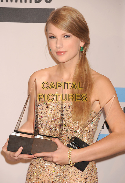 Taylor Swift.at the 2011 American Music Awards - Press Room held at Nokia Theatre at L.A. Live in Los Angeles, California, November 20th, 2011.  .AMA AMAs half length strapless gold sequined sequin beaded dress awards trophies .CAP/ROT/TM.©TM/Roth Stock/Capital Pictures