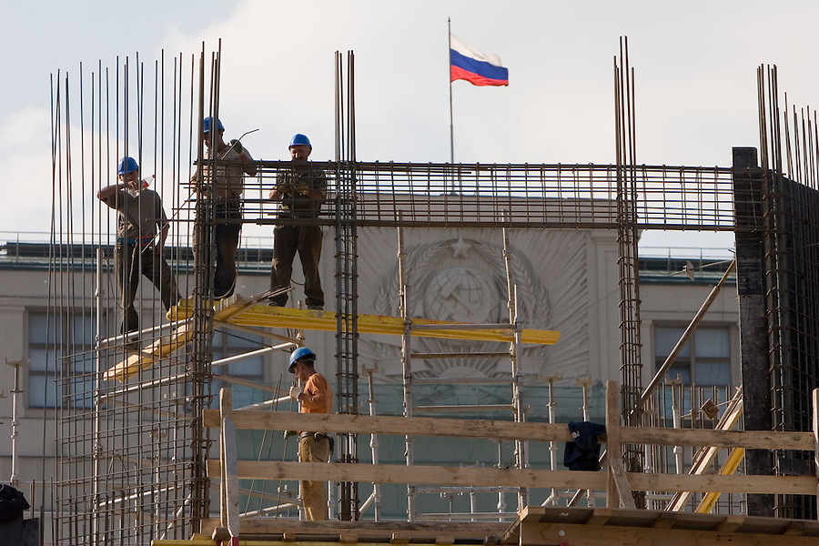 Moscow, Russia, 08/08/2006.&amp;#xA;Builders  at work on scaffolding completely rebuilding the Moskva Hotel on Manezh Square beside the Kremlin. Behind them is the Russian State Duma, which still displays the Communist era hammer and sickle.<br />