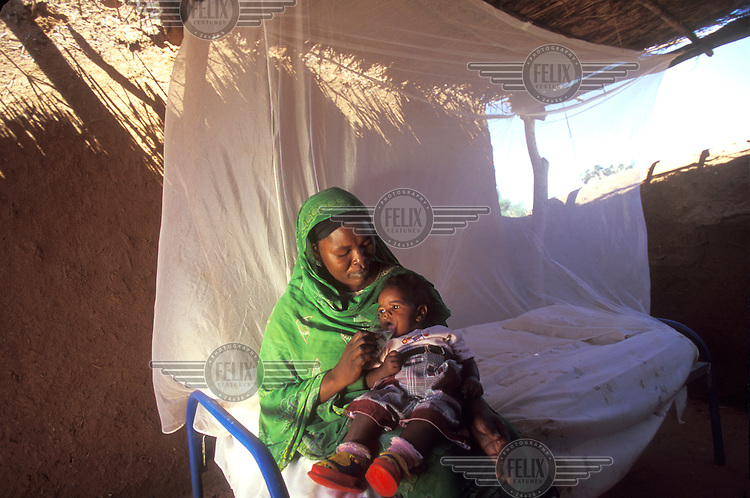 Mother and child - mosquito net over bed. Kordofan, Sudan...© Giacomo Pirozzi/Panos Pictures