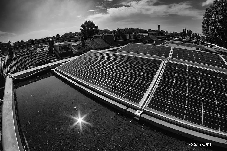 Nederland,Utrecht,   23-06-2016 Zonnepanelen  op het dak van een rijtjeshuis uit 1930 in de Utrechtse wijk Oudwijk. Op de achtergrond de Domtoren .FOTO: Gerard Til / Hollandse Hoogte