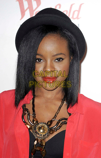 KEISHA BUCHANAN .Arriving at the 'Fashion For Releif' Pop Up Shop Launch at Westfield Shopping Centre, London, England, UK, .5th April 2011..portrait headshot necklace  statement make-up beauty  lipstick straight hair  black hat red jacket .CAP/WIZ.© Wizard/Capital Pictures.