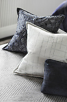 Cushions of varying sizes, textures and patterns on the emperor bed