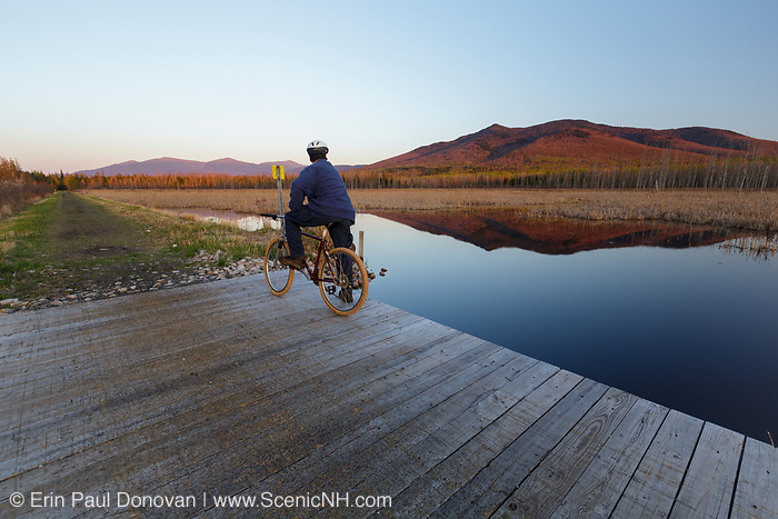 Mountain biker takes in the view from along the Presidential Range Rail Trail (Cohos Trail) at Pondicherry Wildlife Refuge in Jefferson, New Hampshire during the spring months. This trail utilizes the old railroad bed of the Boston & Maine Railroad's Berlin Branch. It was abandoned and track removed in the 1990s.