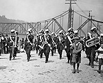 Pittsburgh PA:  Pittsburgh-area Manson marching in the annual St Patrick's Day Parade - 1903.  View of Masonic Band marching down Water Street with crowds lining both sides of the street.
