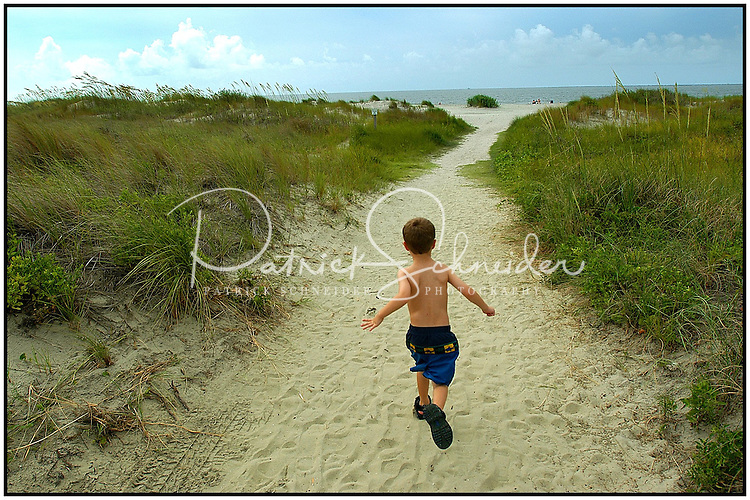 A young boy heads off to the beach along a sandy path. Photo taken on Sullivan's Island near Charleston, SC.   Model released image may be used to illustrate other destinations or concepts.