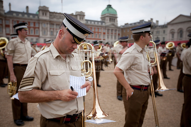 10/06/2013. London, UK. A bandsman of the Coldstream Guards writes notes on his sheet music as the Massed Bands of the British Army's Household Division carry out a dress rehearsal ahead of the annual Beating Retreat ceremony in London today (10/06/2013). The musical event, which takes place on Horse Guards Parade, will be held on the 12th and 13th of June this year, with Prince Philip and the Queen attending. Photo credit: Matt Cetti-Roberts. Photo credit: Matt Cetti-Roberts