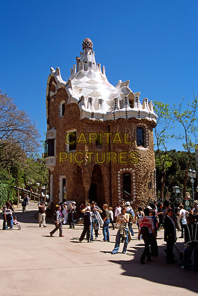 Building with ornate ceramic roof, tourists inside entrance, Guell Park, Barcelona, Spain