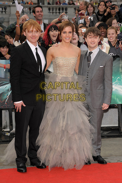 Rupert Grint, Emma Watson, Daniel Radcliffe.'Harry Potter and the Deathly Hallows - Part 2' world film premiere arrivals Trafalgar Square, London, England  7th July 2011.HP7 full length grey gray beige dress gown strapless sleeveless mesh tulle sheer beads beaded black suit.CAP/PL.©Phil Loftus/Capital Pictures.